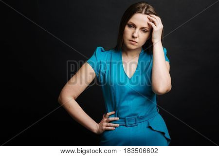 Feeling puzzled . Young perplexed concentrated woman feeling depressed while thinking about something and standing against black background