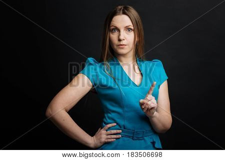 Do not play with me. Confident young pleasant woman gesticulating and demonstrating confidence while raising forefinger up and standing isolated in black background