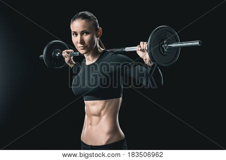 Young Fitness Woman Training With Barbell Isolated On Black.