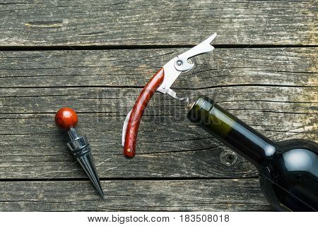 Bottle of wine with corkscrew on wooden table.