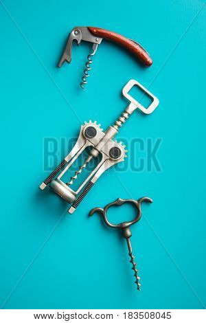 Various types of corkscrews on blue background.