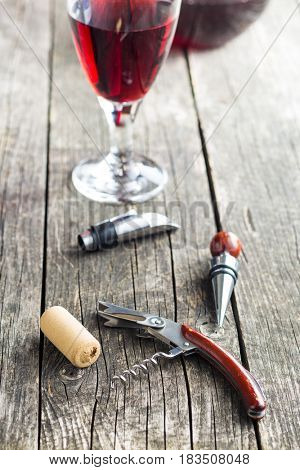 Corkscrew and cork on wooden table.