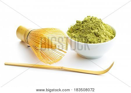 Green matcha tea powder and bamboo whisk and spoon isolated on white background.