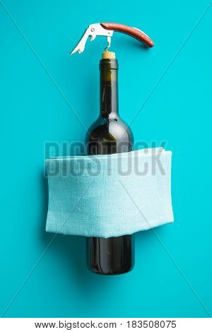 Bottle of wine with corkscrew on blue background. Top view.