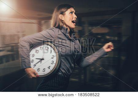 Stressed businesswoman in a hurry running with clock under her arm. Dark background.