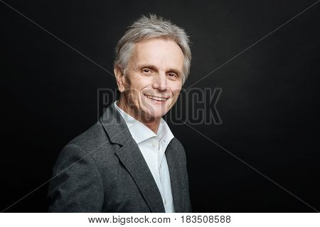 Enjoying every day. Delighted aging pleasant pensioner smiling while sharing positivity and standing isolated in black background