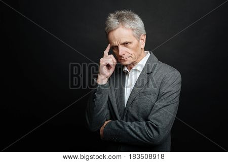 Feeling discomfort. Thoughtful involved aged man thinking while touching his forehead and standing against black background