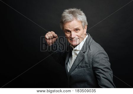 Last time warning you. Aging emotional angry man expressing negativity and warning while showing fist and standing against black background