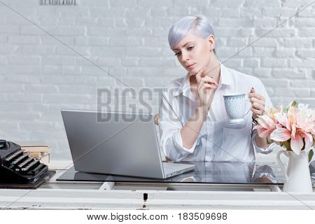 Retro style young woman sitting at desk, working with laptop computer.