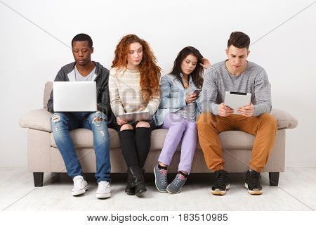 People working with gadgets, addiction concept. Friends sitting on sofa indoors and working on project