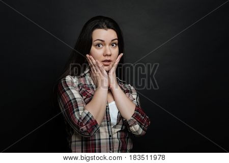 Still can not believe you. Overwhelmed young cute girl demonstrating confused emotions and raising hand to the head while standing isolated in black background