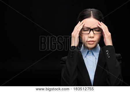 Brunette Businesswoman In Black Suit With Headache Isolated On Black