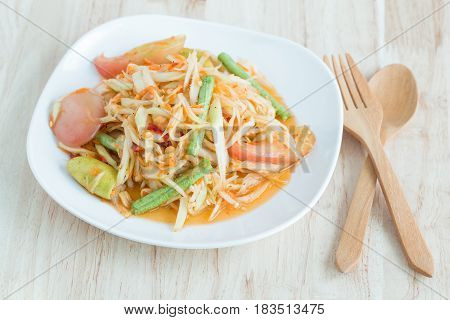 Papaya salad in a white plate on a wooden table,Local thai food