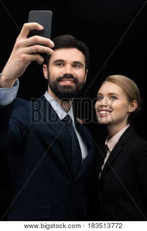 Smiling Business People Taking Selfie On Smartphone Isolated On Black