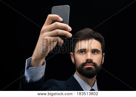 serious businessman taking selfie on smartphone isolated on black