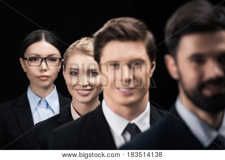 Group Of Young Business People Standing In Row Isolated On Black