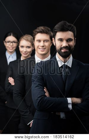 Group Of Confident Business People Standing In Row Isolated On Black