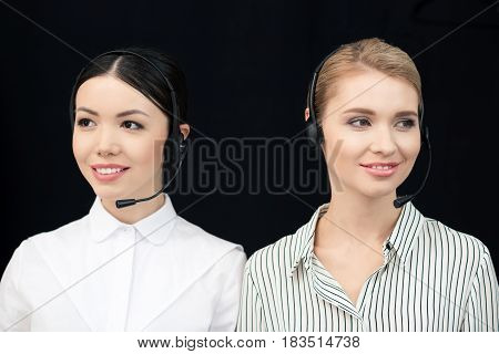 Smiling Call Center Operators In Headsets Isolated On Black