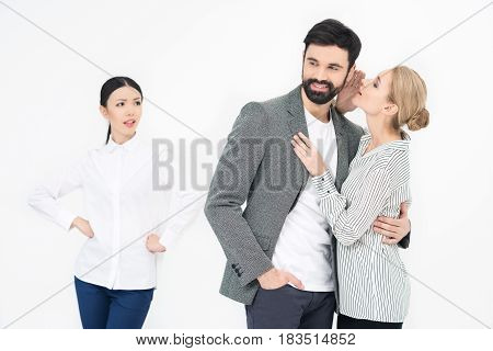 Woman Whispering To Man With Jealous Friend Near By Isolated On White