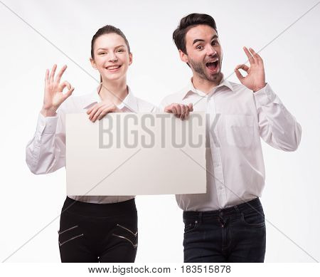 Young happy couple portrait of a confident businessman showing presentation, pointing paper placard gray background. Ideal for banners, registration forms, presentation, landings, presenting concept