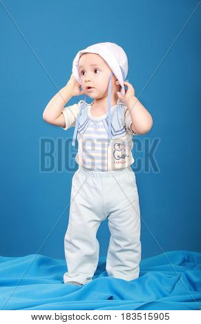 Little boy in sailor suit. Looking to the side holding a hat in his hands