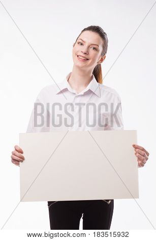 Young happy woman portrait of a confident businesswoman showing presentation, pointing paper placard gray background. Ideal for banners, registration forms, presentation, landings, presenting concept