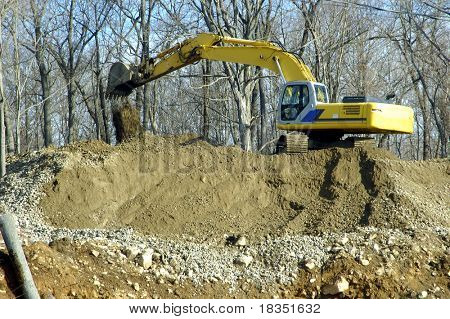 A crane digging up the soil to build houses