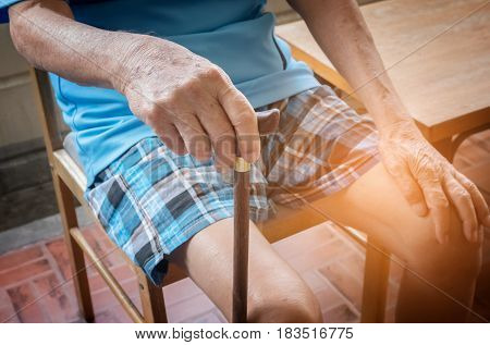 Wrinkled Hand Of Old Senior Man With A Cane Stick