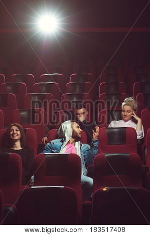 Young adult friends sitting in cinema theater and watching movie. Cinema, entertainment and leisure concept.