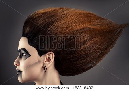 beautiful woman with magnificent hair and dark makeup in profile face