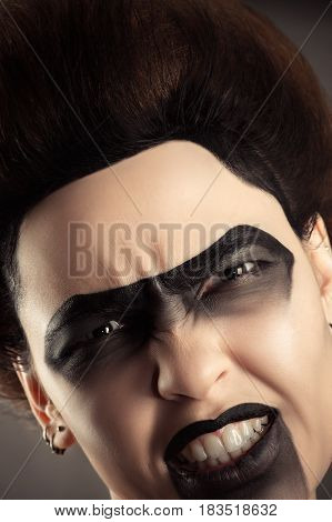 aggressive woman face with creative dark makeup closeup