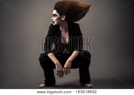 fashionable beautiful woman sitting on squat with lush hair and dark makeup