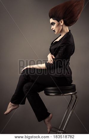 fashionable beautiful business woman sitting on bar stool with lush hair