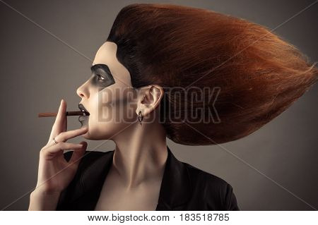 beautiful woman with lush hair with cigarette in mouth