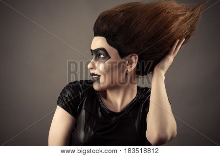 surprised brunette woman touching lush hair on head