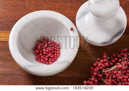 Dry rose pepper in white marble mortar next pestle