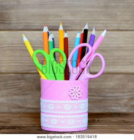 Colored pencils and scissors in a decorative jar. Recycled metal jar for storage of stationery isolated on wooden background. Closeup