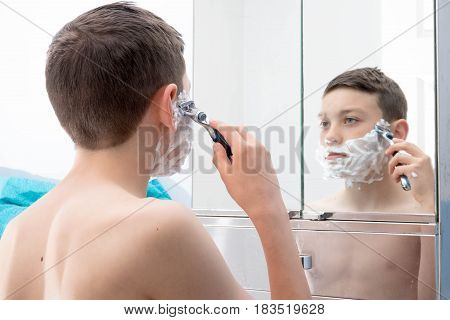 Young teenage boy shaving for the first time