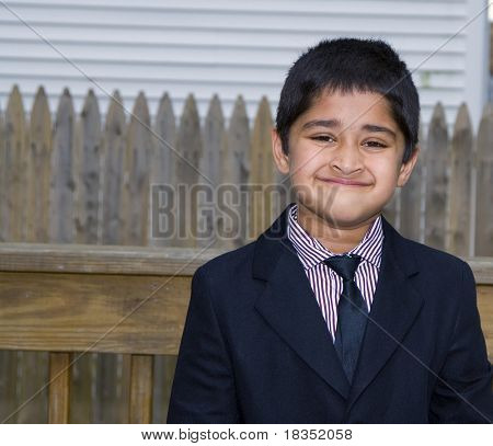 A handsome indian kid formally dressed in a suit