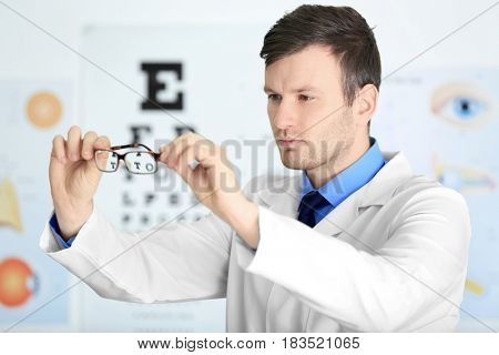Male doctor holding glasses on blurred background