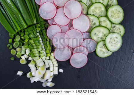 Sliced radish, Cucumber, Green onion on the black slate board, top view. Ingredients for vitamin spring salad