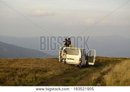 Young people handsome man and pretty girls travel by minibus and enjoy summer vacation on mountain top on foggy sky