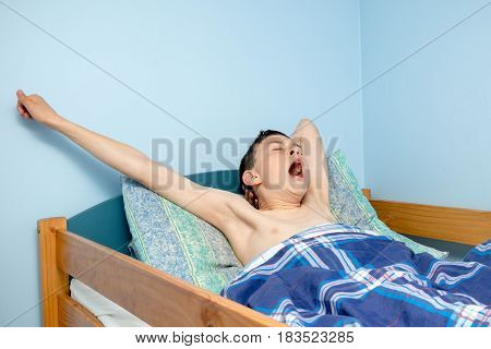 Young caucasian teenage boy waking up in bed