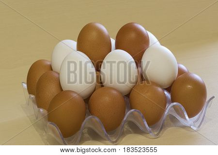 White and dark fresh raw chicken eggs in a rack are stacked for storage