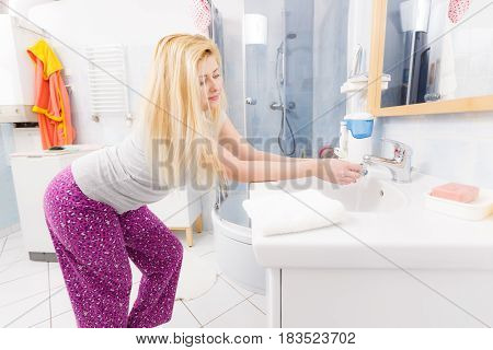 Woman Washing Her Hands In Sink