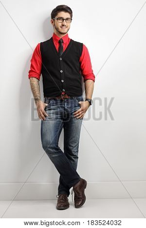 Full length portrait of a tattooed guy leaning against a white wall