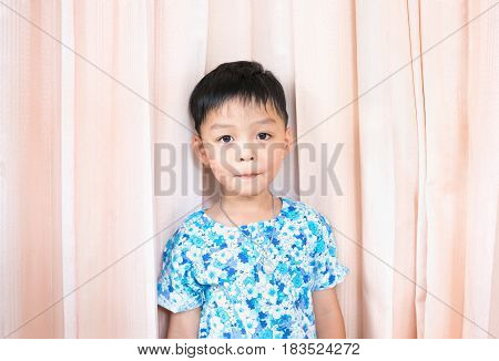 Cute boy wear flower shirt on pink curtain background
