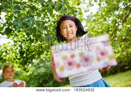 Asian girl with birthday present at birthday party
