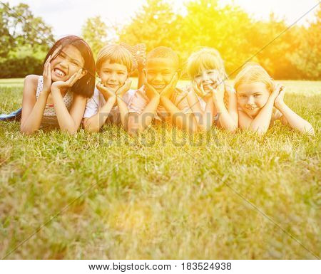 Happy group of interracial kids in the park in summer as integration concept