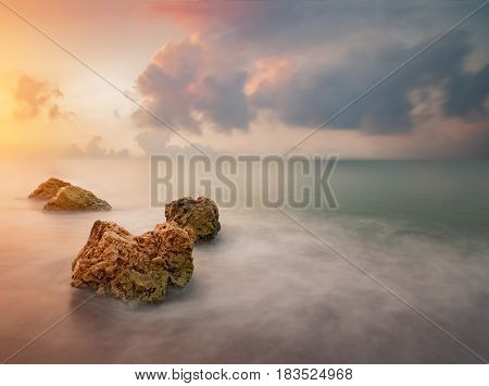 Rocks in sea over dramatic sky during sunrise